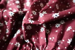 Rippled wine red linen fabric with daisies pattern stock images