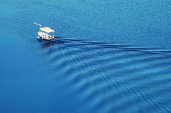 Ripples from above. Wave pattern behind a small boat - seen from above Stock Photo