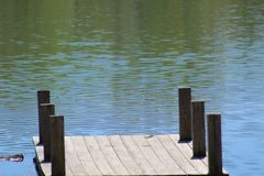 Ripples on the Lake Beyond the Dock. Tiny ripples on the cool waters of the lake beckon just beyond the wooden dock at Vastwood State Park in Kentucky stock photos