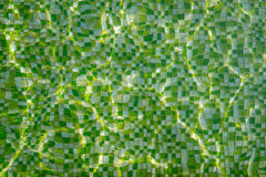 Ripples with lines of reflected light on the green mosaic bottom of swimming pool Royalty Free Stock Photos