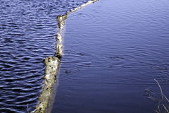 Ripples. A natural log boom protecting the drainage from Upper Lake creates a contrast in ripple effects on the lake surface Stock Images