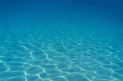 Ripples of sunlight underwater on sandy seabed Stock Photo