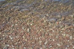 Shallow Water Edge with Stones. Rippling shallow water with brown stones and pebbles below the surface Royalty Free Stock Photography