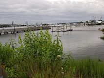 Over the water on a cloudy day. Rippling water on a cloudy summer day with boats in background royalty free stock photo