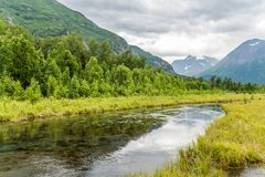Alaska`s Eagle River Reflects the Chugach Mountains. The rippling waters of the calm Eagle River reflect the high mountains surrounding it near Anchorage, Alaska stock images