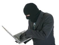 Riprogrammatore di calcolatore - criminale con il computer portatile Fotografia Stock