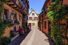 RIQUEWIHR,法国- 2017年7月17日:有传统五颜六色的房子的美丽如画的街道在阿尔萨斯酒路线的Riquewihr村庄 免版税库存照片