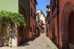 RIQUEWIHR,法国- 2017年7月17日:有传统五颜六色的房子的美丽如画的街道在阿尔萨斯酒路线的Riquewihr村庄 免版税库存图片