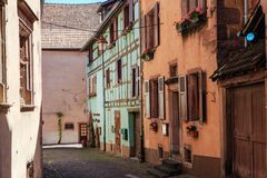 RIQUEWIHR,法国- 2017年7月17日:有传统五颜六色的房子的美丽如画的街道在阿尔萨斯酒路线的Riquewihr村庄 图库摄影