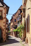 RIQUEWIHR, FRANCE - JULY 17, 2017: Picturesque street with traditional colorful houses in Riquewihr village on alsatian wine route Stock Photos
