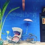 Riquexó velho na frente da casa azul Fotos de Stock Royalty Free