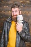 Riqueza y bienestar Inconformista barbudo brutal del hombre llevar la chaqueta de cuero y sostener el dinero del efectivo Negocio foto de archivo