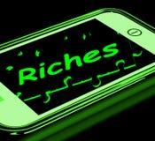 Riquezas en Smartphone que muestra riqueza Imagenes de archivo