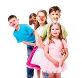 Rir crianças com palhaço cheira estar um perto foto de stock