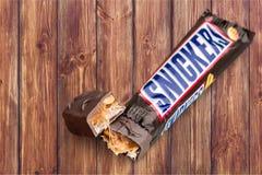 Rir debochadamente a barra de chocolate no fundo de madeira imagens de stock royalty free