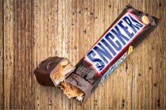 Rir debochadamente a barra de chocolate no fundo de madeira foto de stock royalty free