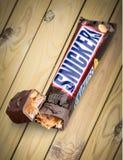 Rir debochadamente a barra de chocolate no fundo de madeira fotografia de stock