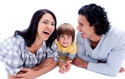 Rir parents com seu filho que encontra-se no assoalho imagens de stock