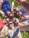 Rire d'amie de femmes prenant un selfie se trouvant sur l'herbe Images stock
