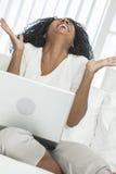 Rire d'ordinateur portable de femme d'Afro-américain Images libres de droits