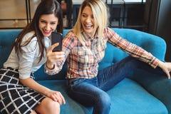 Rire de deux femmes tout en prenant un selfie Image stock