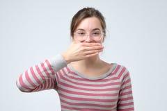 Rire de dissimulation de visage de jolie femme espiègle timide images stock