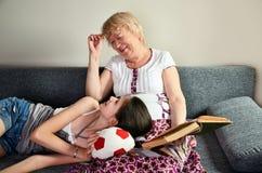Rire de grand-mère et de petite-fille se reposent sur le divan et regardent Photos libres de droits