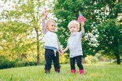 Rire de sourire de fille et de garçon tenant des mains et ondulant les drapeaux américains et canadiens, extérieur en parc Photographie stock