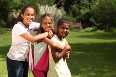 Rire et étreintes heureux de trois amis d'école Photographie stock