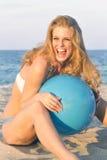 Rire femelle blond avec la bille de plage Image libre de droits