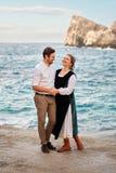 Rire les couples joyeux de sourire de famille se tient doucement étreignant avec le fond et les roches bleus de mer dans de rétro Image libre de droits