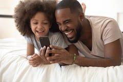 Rire noir heureux de téléphone d'utilisation de papa sur le lit avec la fille photographie stock