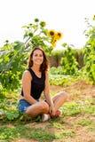 Rire se reposant de jeune femme sous un tournesol à la lumière du soleil images stock