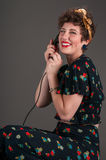 Rires de pin-up de fille tandis qu'au téléphone démodé Photo stock