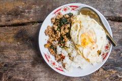 Ris för bästa sikt som överträffas med stekt under omrörning griskött och basilika med det stekte ägget som förläggas på en tabel Royaltyfri Fotografi