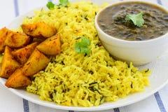 Ris för Sindhiuppläggningsfatvitlök, stekte potatisar och linser Arkivbild