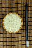 Ris i bunke med pinnar på traditionellt asiatiskt mattt för platta royaltyfria foton