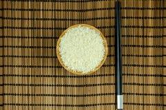 Ris i bunke med pinnar på traditionellt asiatiskt mattt för platta arkivbild
