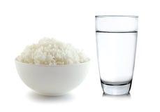 Ris i en bunke och ett exponeringsglas av vatten på vit bakgrund royaltyfri bild
