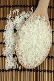 Ris i träsked på traditionellt asiatiskt mattt för platta arkivfoton