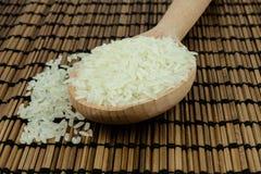 Ris i träsked på traditionellt asiatiskt mattt för platta stock illustrationer