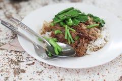 Ris med griskött som låtas småkoka i skyn Arkivfoton