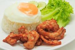 Ris med stekt griskött och det stekte ägget Arkivbild