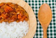 Ris och röd curry i trämaträtt arkivbild