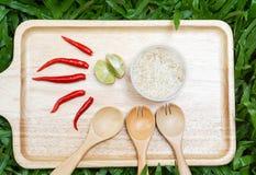 Ris röd chili, limefrukt på trämagasinet Royaltyfri Bild