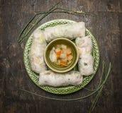 Ris rullar med en genomskinlig nudel inom sidorna av lök- och grönsakbuljong på bästa sikt för mörk trälantlig bakgrund Royaltyfri Foto