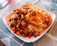 Ris som överträffas med finhackad grisköttbasilika och omelett arkivfoton