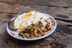 Ris som överträffas med stekt under omrörning griskött med basilika och det stekte ägget som förläggas på tabellen med portionen, Arkivbild