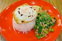 Ris som överträffas med stekt under omrörning griskött, basilika och det stekte ägget (solig sid Royaltyfria Bilder