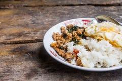 Ris som överträffas med stekt under omrörning griskött och basilika med det stekte ägget som förläggas på tabellen, ordnar till f Royaltyfri Foto